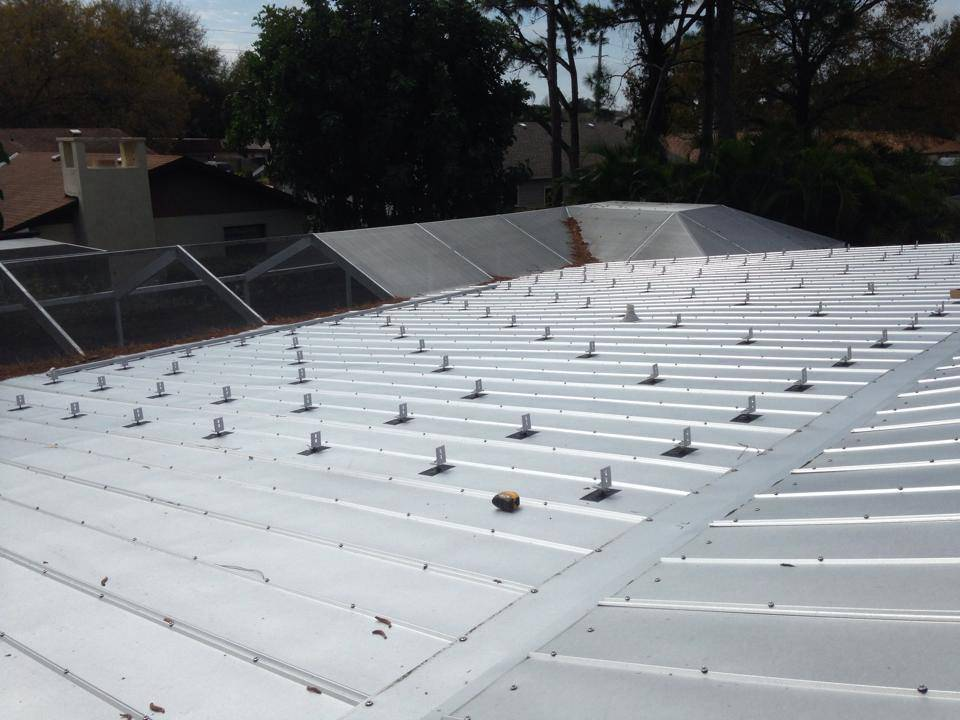 Solar Mounts being installed on metal roof