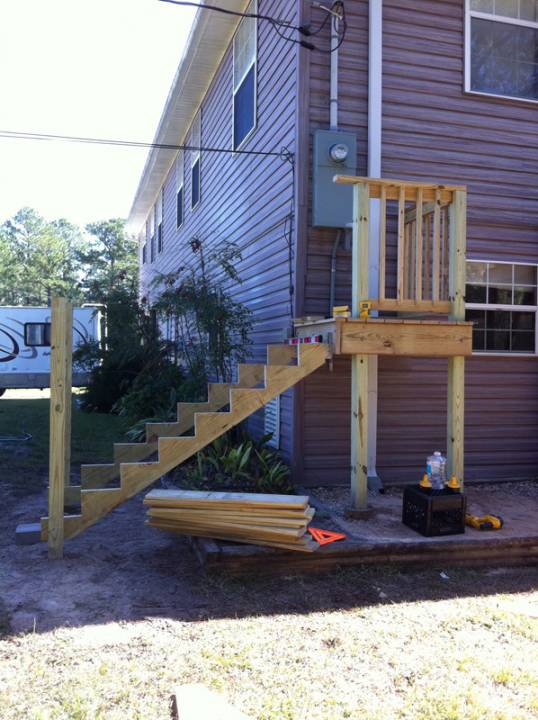 Custom built staircase to meet flood requirements and meter access on a solar battery backup system installed in Navarre, FL