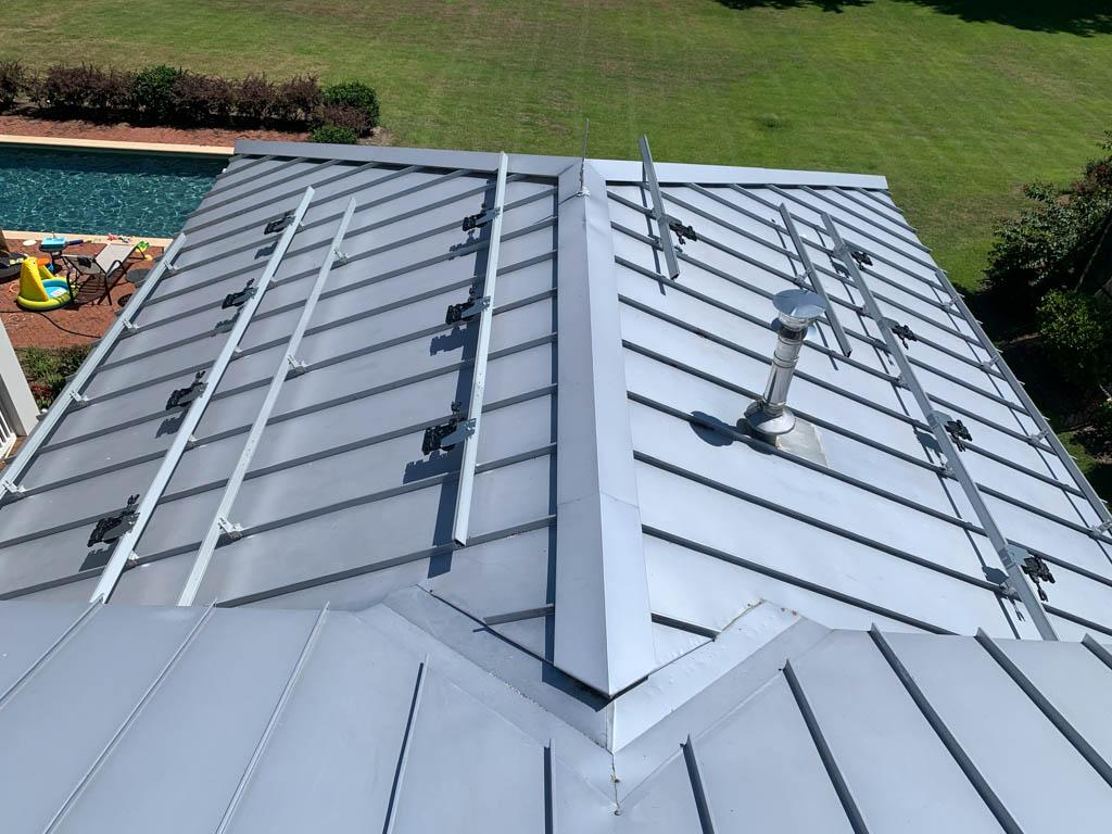 Roof view of solar racks and micro inverters installed on a metal roof in WInter Haven, FL